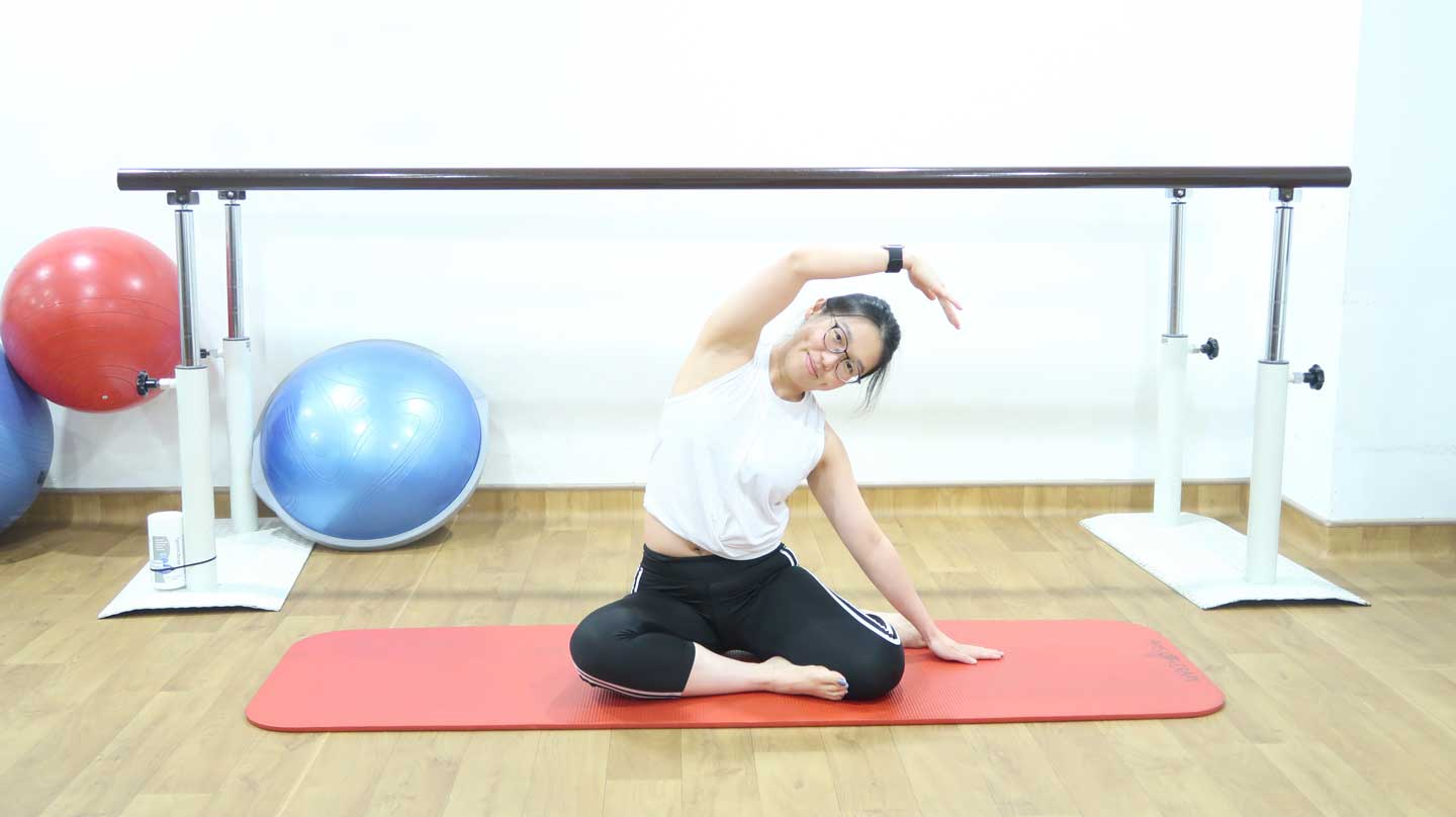 A Clinical Pilates Instructor Shows the ending position of the mermaid pose, used to treat Scoliosis.