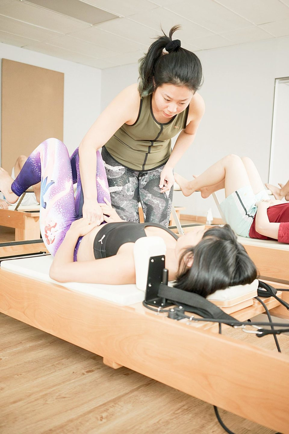 An Instructor helps a client to engage their core (the transverse abdominus) during Clinical reformer training.
