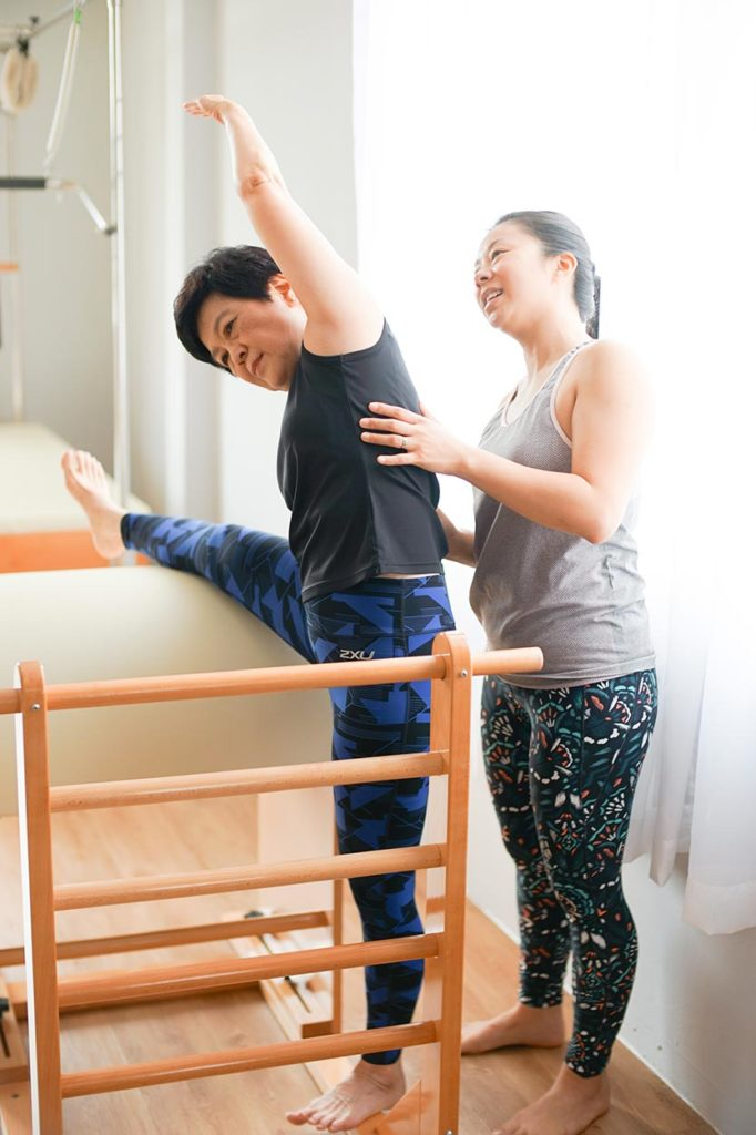 A Clinical Pilates client does a side-bend over the special equipment (called the ladder barrel). The exercise helps mobilise stiff spine segments.
